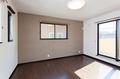 ダーク色の床とブラウンのアクセントクロスを採用した落ち着いた寝室。