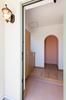 ドアを開けると広々とした玄関の奥にオレンジ色が特徴的なアールの出入り口。