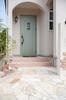 乱石貼りのアプローチを通ると、ミストグリーンにアイアンのデザインが施された玄関ドアがお出迎え。