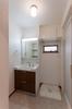 洗面室は洗面化粧台の裏に収納棚を。洗濯機上にも収納できるように、可動棚を設けています。